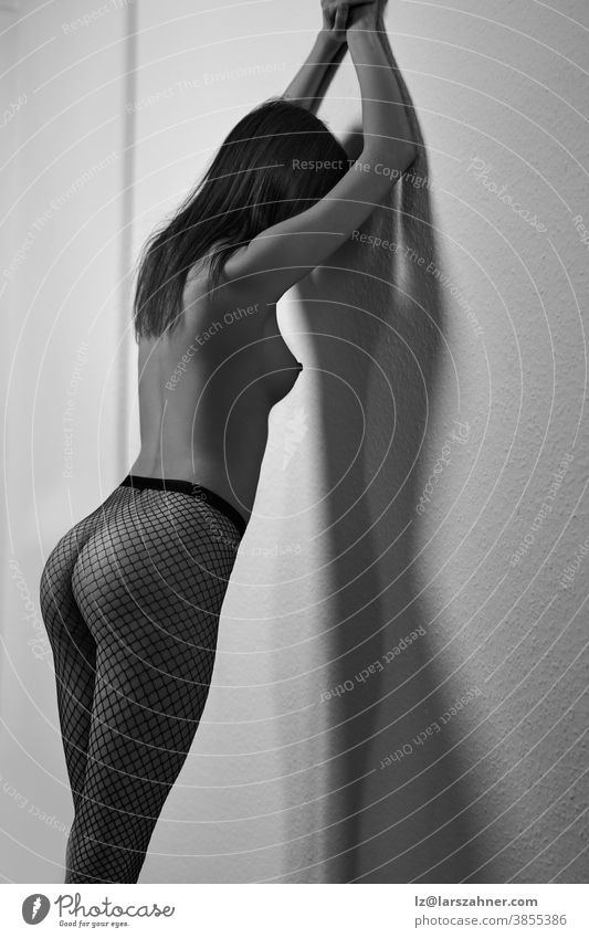 Sexy topless young woman in fishnet stockings leaning her hands up against a wall and turning to give the camera a sultry glance in a greyscale portrait sexy