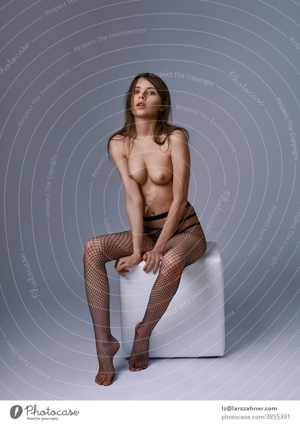 Alluring topless young woman in fishnet stockings posing sitting on a cube looking at the camera with parted lips in a provocative sensual pose alluring tights