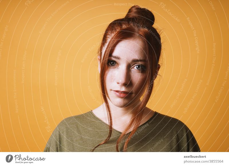 cool young woman with red hair messy bun hairstyle and loose strands front adult person portrait people studio female beautiful attractive girl pretty caucasian