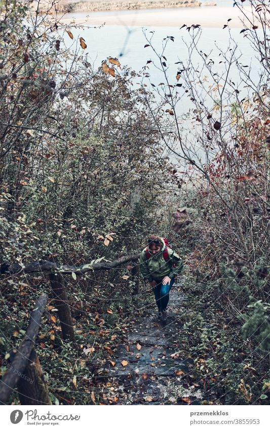 Woman going upstairs on trekking path during trip on autumn outdoors destination hiking holiday vacation hiker explore landscape woman lifestyle female nature