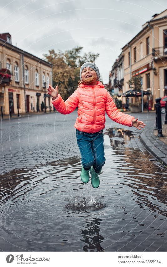 Little girl jumping in the puddle on rainy gloomy autumn day raining outdoors little seasonal fall childhood beautiful weather outside kid wet holding city town