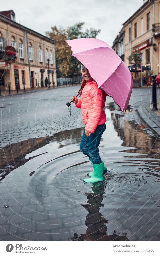 Little girl holding big pink umbrella walking in a downtown on rainy gloomy autumn day raining outdoors little seasonal fall childhood beautiful weather outside