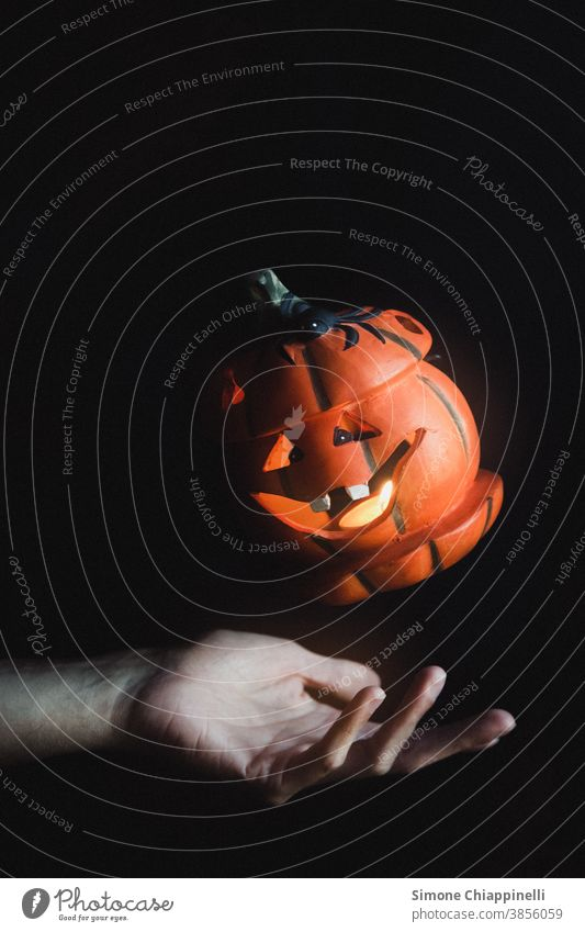Floating halloween pumpkin orange fall autumn seasonal october decoration levitation jack o lantern Magic Hand black background Dark holiday celebration