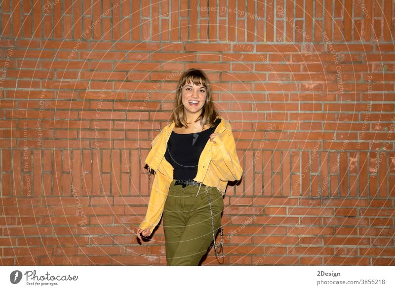 Beautiful young woman stands near an old brick wall in the city at night standing attractive smiling happy casual attire female person beautiful lifestyle