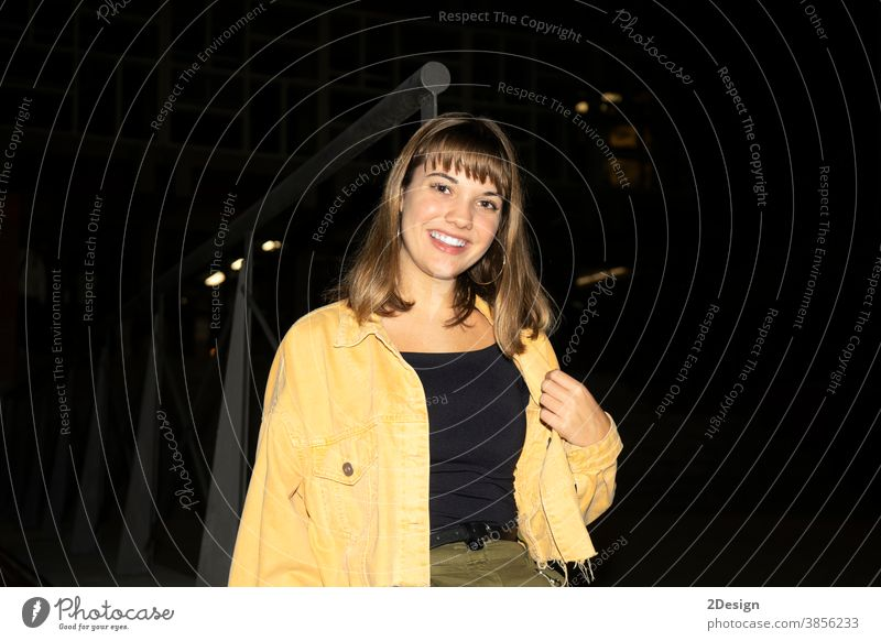 Young beautiful girl sitting in a bench in a public city park at night while looking to camera young female 1 attractive pretty happy outdoor woman person