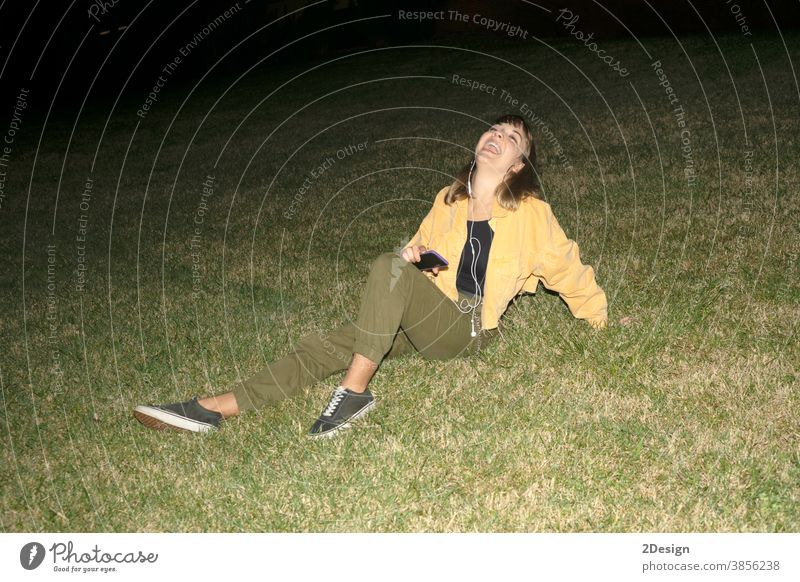 Young attractive blond girl sitting on grass in a park at night young female 1 beautiful pretty happy outdoor woman person lifestyle portrait happiness fashion
