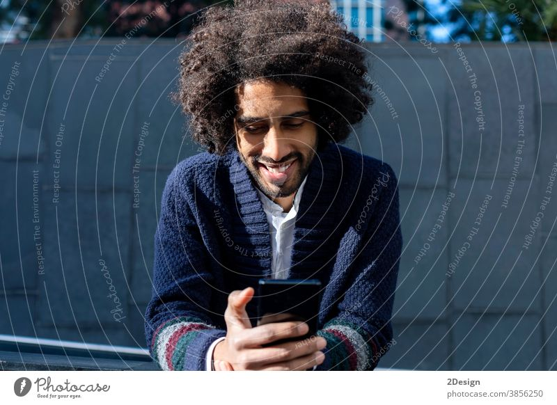 Smiling African American guy writes SMS to friends on phone. man 1 afro mobile smiling happy male technology mobile phone message black african outdoor portrait