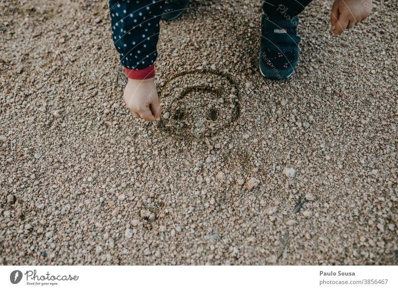 Child drawing a smile on sand Smiley childhood Children's game Infancy Joy Exterior shot Childhood memory Playing Colour photo Toddler Happiness Multicoloured