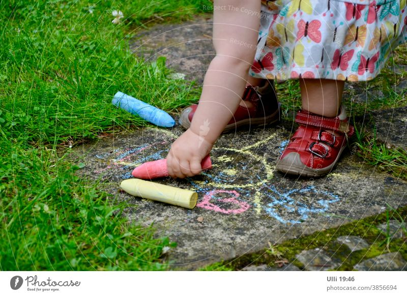 grandchild paints an old garden path in a colour matching the dress....... Child Childlike Summer's day Garden Garden path Stone slab Draw crayons Blue Red