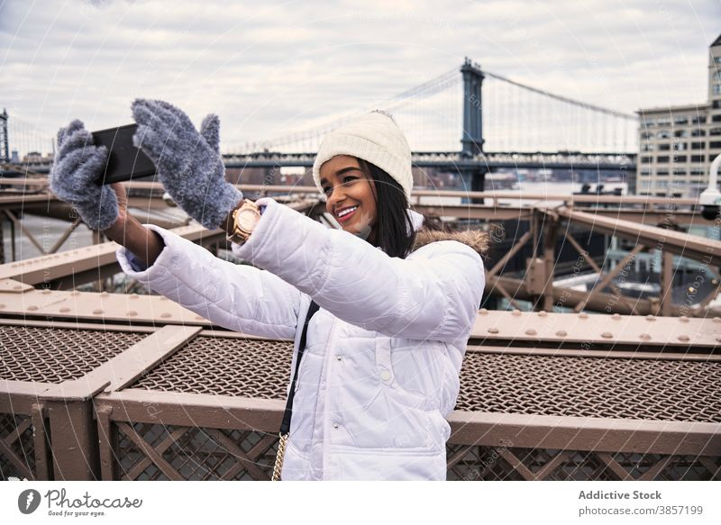 Smiling ethnic woman taking selfie in city smartphone warm clothes outerwear season cheerful self portrait using female black african american new york