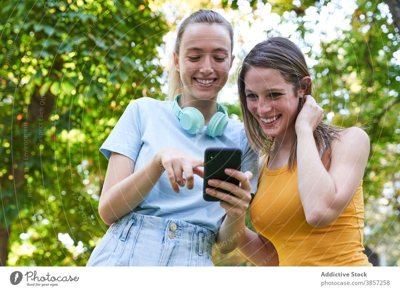 Female hipsters with smartphone walking in city girlfriend using discuss street share together mobile cheerful laugh happy urban show demonstrate gadget device