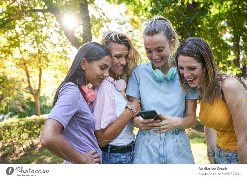 Group of female hipsters with smartphone walking in city girlfriend using discuss street share together mobile cheerful laugh happy urban group show demonstrate