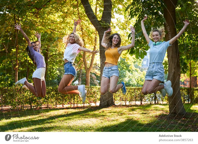 Group of diverse teen girlfriends jumping high in park having fun summer happy cheerful together teenage women multiracial multiethnic female friendship