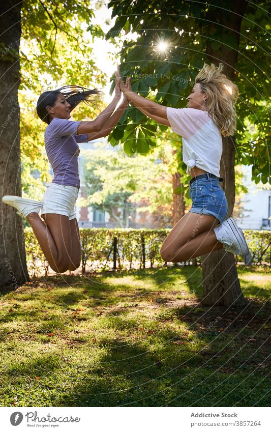 Carefree young girlfriends jumping in summer park having fun clap high five happy cheerful together teenage women multiracial multiethnic diverse female