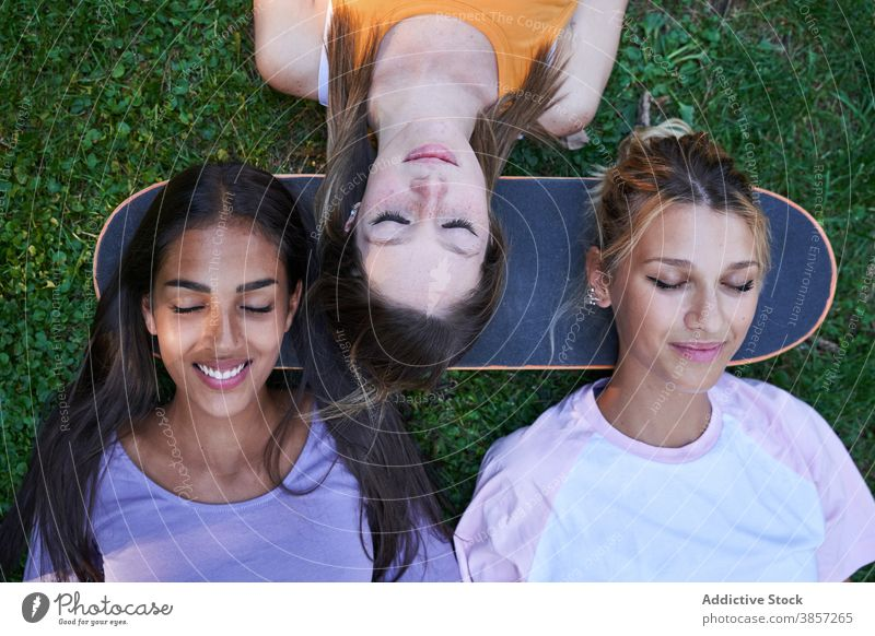 Young women with skateboard lying on green grass girlfriend park chill summer happy cheerful together rest teenage multiracial multiethnic diverse female