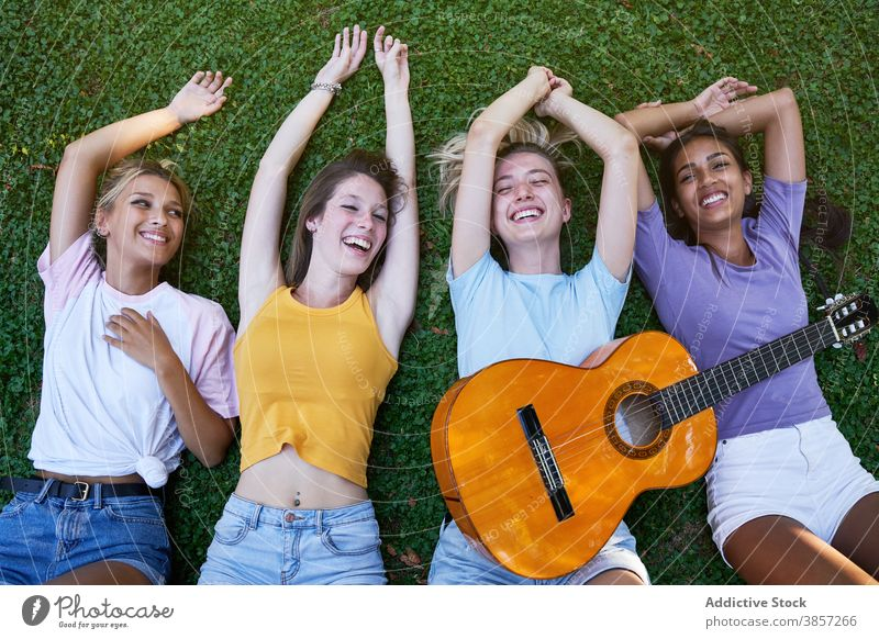 Happy multiracial teenagers with guitar enjoying summer day in park girlfriend chill lying happy cheerful together rest women multiethnic diverse female