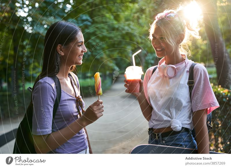Happy girlfriends with ice cream and drink having fun in park summer popsicle happy cheerful chat together diverse multiethnic multiracial teen female