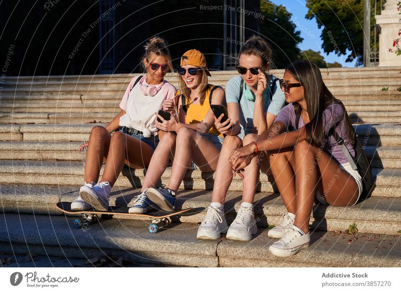 Group of teenagers with smartphones sitting on steps in city girlfriend urban together cheerful using trendy mobile women young multiracial multiethnic diverse