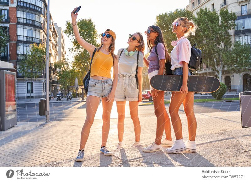 Positive female teenagers taking selfie in city girlfriend urban summer happy trendy cheerful together group skateboard active phone mobile street diverse