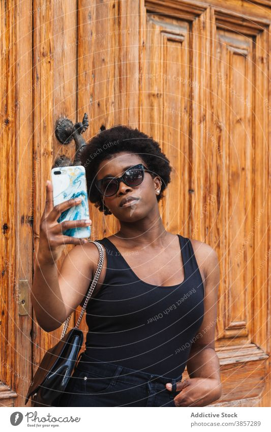 Young black woman taking selfie on smartphone confident using device social media digital browsing memory female gadget mobile stand online hand in pocket