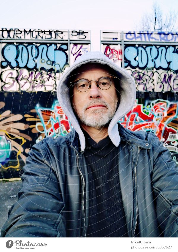 Old graffiti fan in front of a graffiti wall Graffiti Man Human being Wall (barrier) Masculine Adults street art urban City Face Eyeglasses Hooded (clothing)