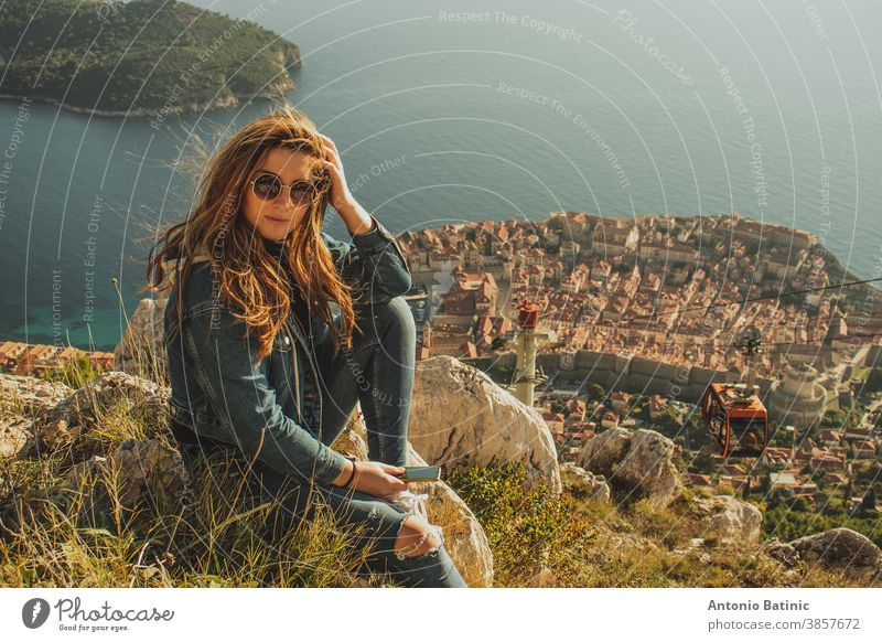 Attractive brunette sitting on the Srd hill above the city of Dubrovnik, observing the city in the distance. Wind blowing her hair above the ancient famous landmark town