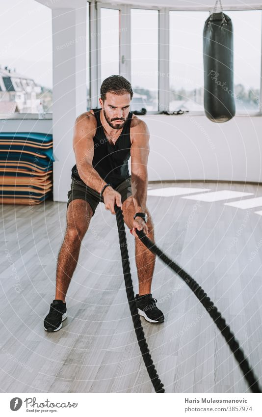 man working out with ropes in gym abdominal abs adult athlete athletic attractive male biceps body building bodybuilding caucasian chest dedication equipment
