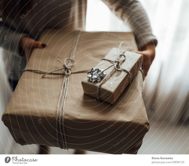 Young woman holds in hands stacked Christmas gift boxes in craft paper with juniper. Christmas presents concept. christmas merry christmas new year women