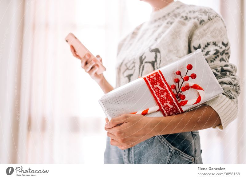 Young unrecognizable woman watching her mobile phone holds in a gift box in metallic paper with red twine and candy. Christmas New Years present. christmas
