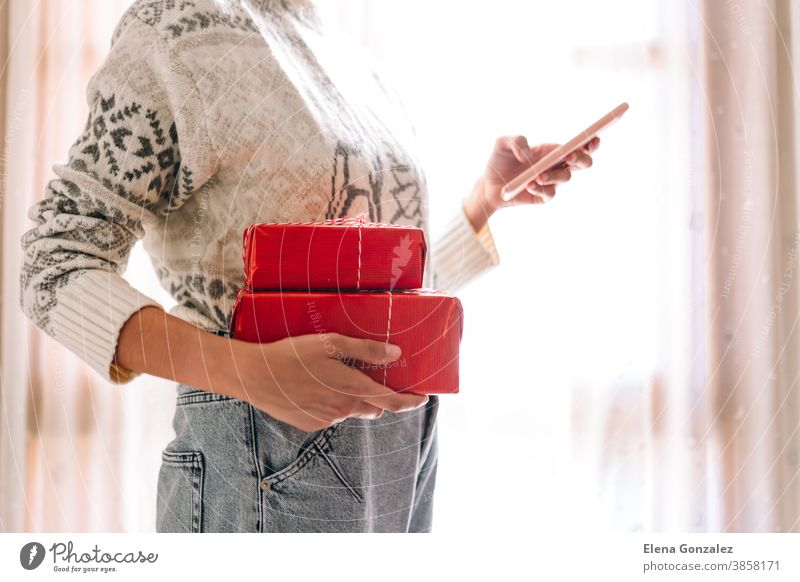 Young unrecognizable watching her mobile phone woman watching her mobile phone holds red gift boxes. Christmas New Years present. christmas merry christmas