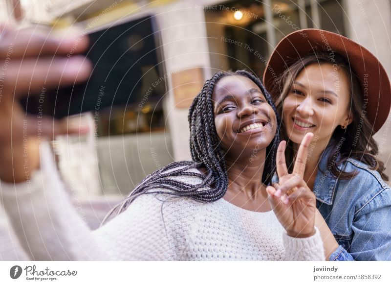 Two beautiful multiethnic women making selfie and grimacing woman smartphone lifestyle young female girl smile street happy casual urban mobile hairstyle