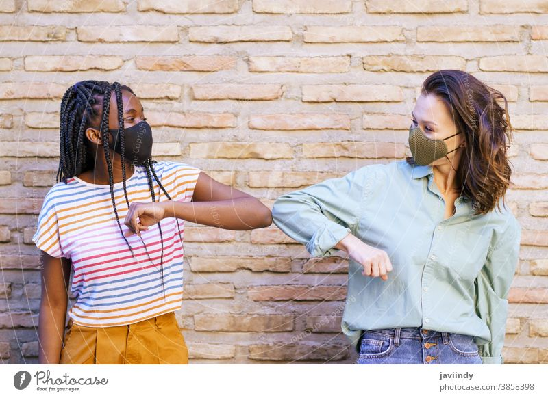 Multiethnic young women wearing masks greeting at each other with their elbows people social distancing woman pandemic virus coronavirus lifestyle covid