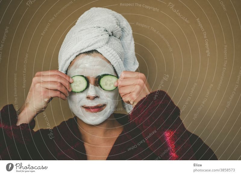 Woman with bathrobe and towel on her head enjoys a face mask and holds two slices of cucumber in front of her eyes. Wellness, face care. Face mask