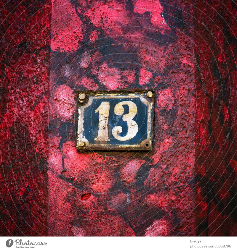 Weathered house number 13 on red - black house wall. Number 13 House number Old Rust Red Black Colour Superstition Digits and numbers Central perspective