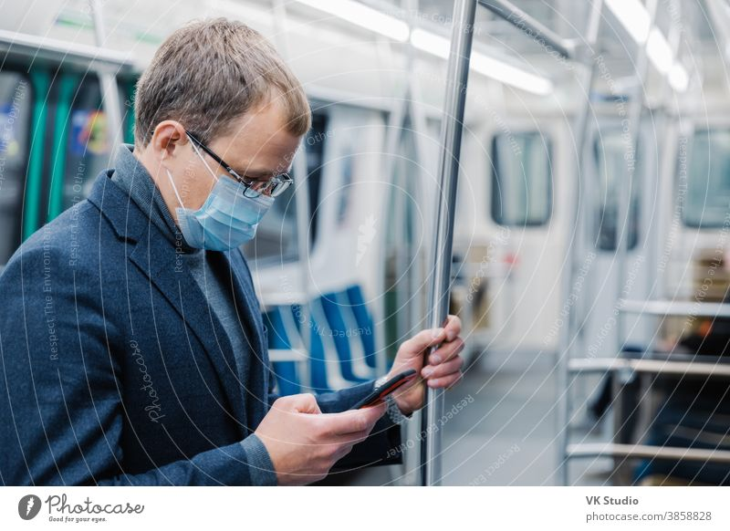 Serious man commutes to work in underground wears virus protective mask being always in touch with modern cellular poses in empty subway or metro. Distance concept. Public transport during coronavirus
