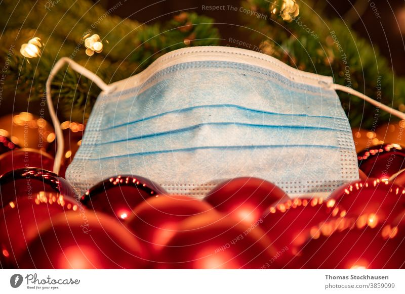 group of red christmas balls and a mouth protection mask, lights in the background. Symbol for impact of covid-19 virus in christmas season 2020 and 2021