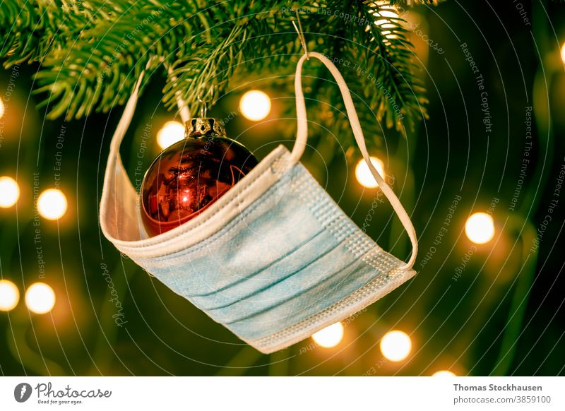 red christmas ball and a mouth protection mask on a pine branch, lights in the background. Symbol for impact of covid-19 virus in christmas season 2020 and 2021
