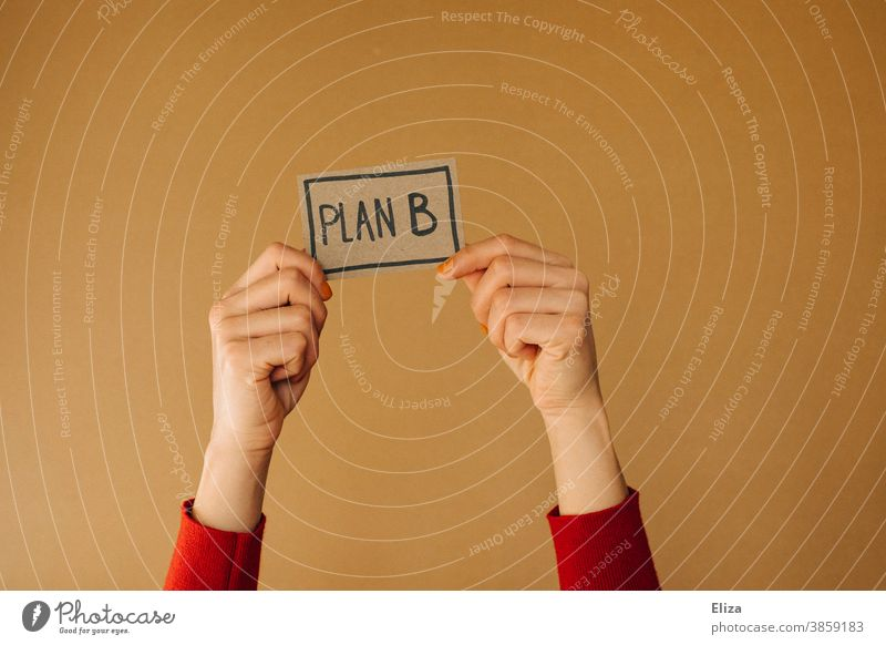 Hands hold a sign with the inscription PLAN B. Alternative life path. Plan B alternative path of life Direction solution Planning Business training