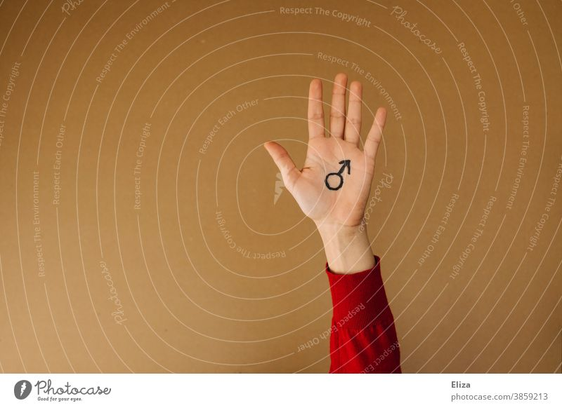 A hand on which the Mars symbol for masculinity is painted against a neutral brown background Hand Man Masculine Gender symbol man up male sex toxic masculinity