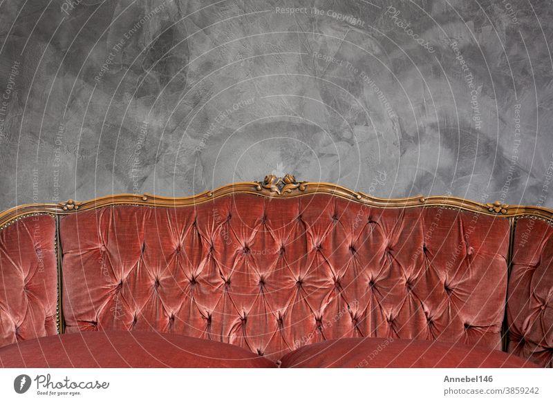 Antique luxury sofa detail against concrete wall background texture, beautiful vintage design copy space interior furniture room home retro floor house elegance