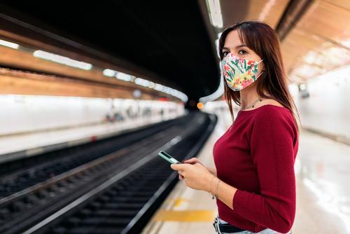 Young woman using smartphone at train station portrait mask face lifestyle platform modern public technology transport caucasian passenger people transportation