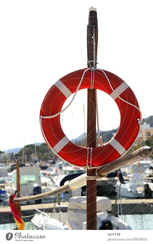Ready for use - red white neutral life ring is attached to a wooden pole Life belt quay wall Harbour misfortune Help Protection Safety First Aid Water boat port