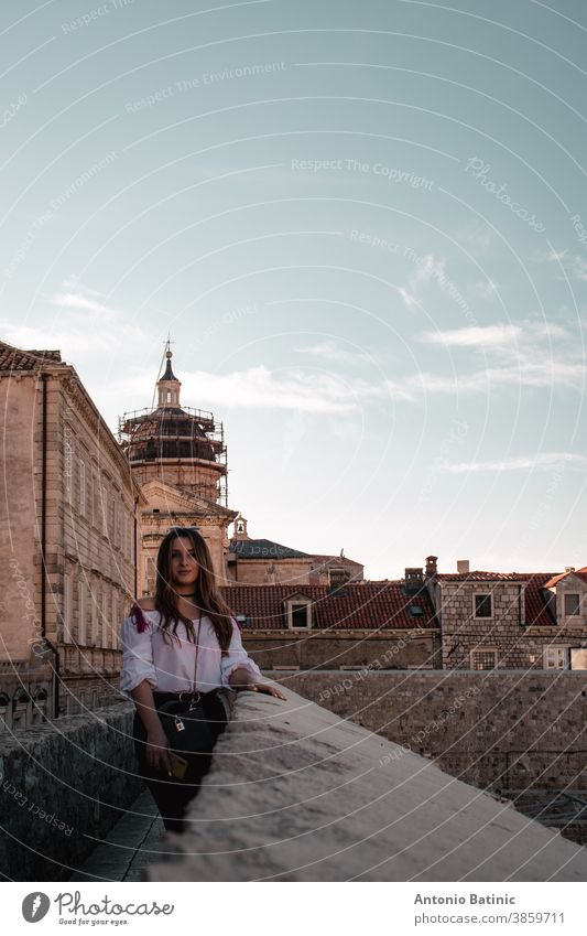 Moody vertical portrait of a brunette standing at the walls of Dubrovnik city vacation famous medieval lifestyle stone beach panoramic pose covid modern leather