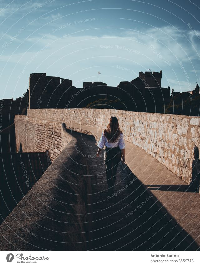 Vertical shot and rear view of an attractive girl walking along the city walls of Dubrovnik town. Dark moody edit with black and orange highlights holiday relax