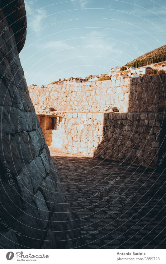 Looping circle area surrounded by walls around the Minceta castle tower in the old city of Dubrovnik being lit by strong sunlight and creating shapes with shadows