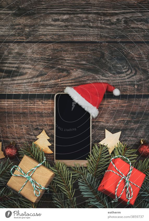 Christmas concept background.Smartphone with santa claus hat and Christmas tree branches christmas christmas tree smartphone christmas background christmas eve