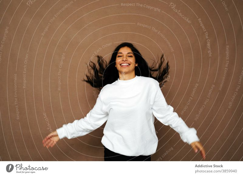 Delighted woman with flying hair in studio having fun laugh white sweatshirt casual style cheerful female ethnic enjoy modern positive young fashion delight