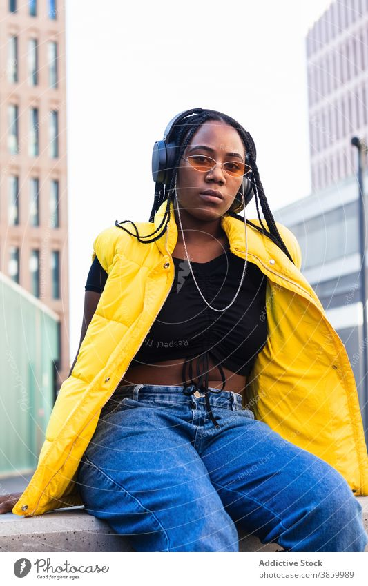 Glad African American female listening to music in city woman town street enjoy downtown style trendy young black african american ethnic favorite modern