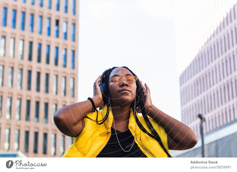 Glad African American female listening to music in city woman town street enjoy downtown style eyes closed trendy young black african american ethnic favorite