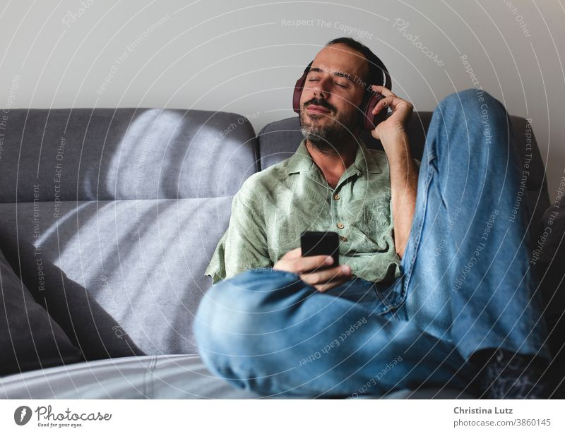 Man sitting on sofa in the living room listening to music with headphones man relax home people mobile person communication telephone smiling white technology